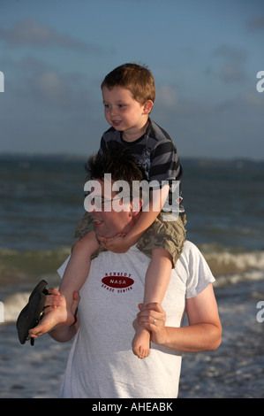 mid thirties dad wearing sunglasses carrying three year old son on his shoulders whilst walking on the beach in - Stock Photo