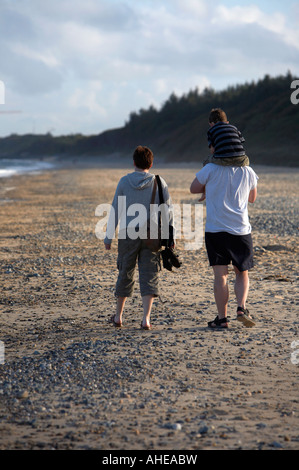 young family walking along the beach mother father and three year old son on fathers shoulders in county wexford Stock Photo