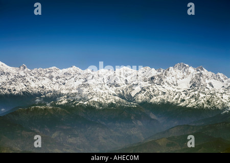 Wide expansive aerial view of Snowcapped Himalayan peaks over their foothills below a clear blue sky - Stock Photo