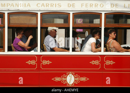 Tourists siting in an antique Lisbon red tram used for sightseeing tours in Praca do Comercio square, Lisbon Portugal - Stock Photo