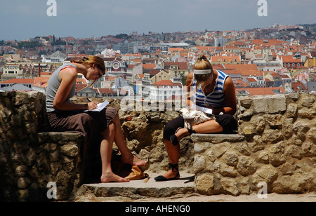 Young tourists writing letters on the fortification wall of Sao Jorge Castelo or Saint George Castle overlooking - Stock Photo