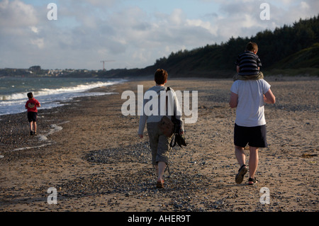 family walking along the beach seven year old in front with dad carrying three year old boy in county wexford - Stock Photo
