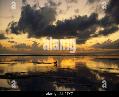Looking over calm waters at sunrise at silhouette of lone fisherman off Sanur Beach on the South East Coast Bali - Stock Photo