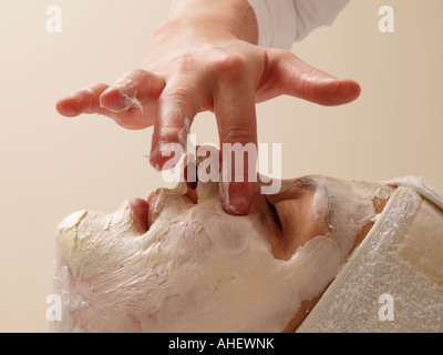 Beautician applying creme on a woman s face hand fingers side profile skin care cosmetics - Stock Photo