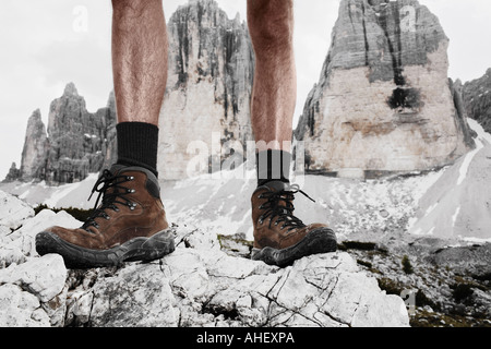 Shoes Of Mountain Climber Standing In Front Of Summits Tre Cime Three Peaks Dolomites Alps Italy - Stock Photo