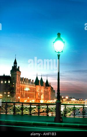 Paris, France, French Monument 'Pont Au Change' Bridge with the Conciergerie Building, Street Lamps at Night - Stock Photo