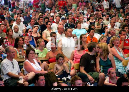 People watching live footage of World Cup football match - England versus Portugal - on a large screen in large hall. Malvern UK