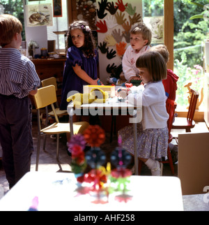 A group of children playing together at a table inside in a nursery school Vancouver Island, British Columbia, Canada - Stock Photo