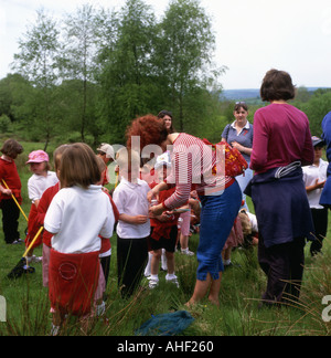 Primary school children with butterfly nets and teachers on nature walk school trip in spring in  Llandeilo Carmarthenshire Wales UK  KATHY DEWITT