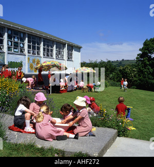 Pupils playing oudoors in summer sunshine at a Welsh school in the town of Llandeilo Carmarthenshire (Dyfed) Wales - Stock Photo