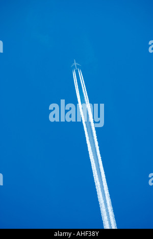 Jet airplane with four merging contrails - Stock Photo