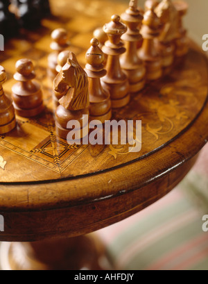 Close-up of carved wooden chess pieces on inlaid antique table - Stock Photo