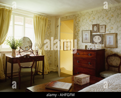 Pastel yellow curtains in traditional country bedroom with patterned  neutral wallpaper and antique chest of. Bedroom with patterned curtains and dressing table in English