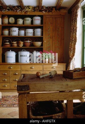 Old enamel storage cannisters on antique pine dresser in cottage kitchen with butcher's block - Stock Photo