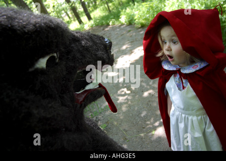 little red riding hood meets the wolf on the path - Stock Photo