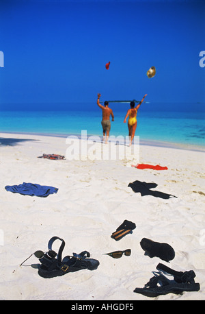 Couple tossing clothing while running across white sandy shore toward blue ocean waters on first day of island holiday - Stock Photo