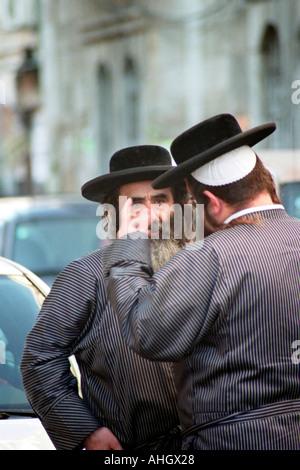 Israel Jerusalem Mea Shearim neighbourhood Two ultra orthodox Religious Jews talking in the street - Stock Photo