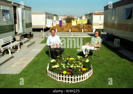 Couple sitting in the sun on grass lawn next to small flowerbed outside their static caravan Trecco Bay Porthcawl - Stock Photo