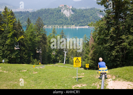Lady on summer toboggan ride down Straza ski slope above Lake Bled Bled Slovenia - Stock Photo