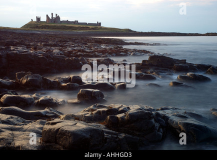 Dunstanburgh Castle at sunset Northumberland Coast Stock Photo
