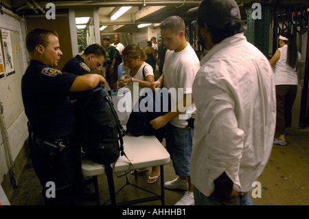 NYPD officers perform random checks on commuters bags at the West Fourth Street subway station in Greenwich Village - Stock Photo