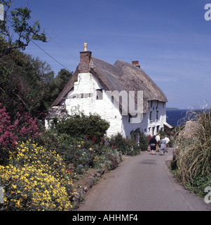Church Cove near Mullion small coastal hamlet country lane with thatched roofed cottage distant and walkers - Stock Photo