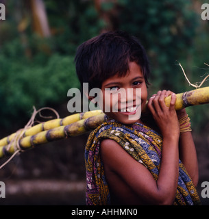 INDONESIA Southeast Asia Lombok Kuta Smiling boy with a sarong over his shoulder carrying sugarcane. - Stock Photo