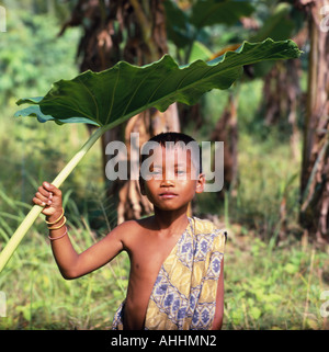 INDONESIA Southeast Asia Lombok Kuta Boy with a sarong over his shoulder using a large leaf as sun shade - Stock Photo