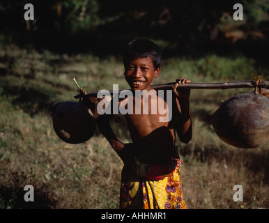 INDONESIA Southeast Asia Lombok Timur NTB Mawon near Kuta Smiling young boy in floral sarong holding pole of dried - Stock Photo