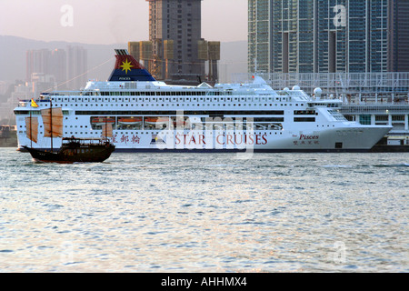 Old Tourist Junk in front of Enormous New Luxury Cruise Ship, TST, Hong Kong, China - Stock Photo