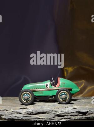 1950s toy clockwork tin car on dark background - Stock Photo
