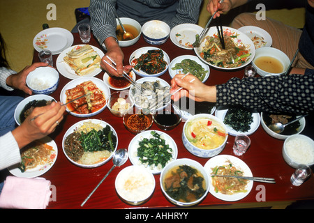 Family sitting at dinner table eating variety home made Korean foods - Stock Photo