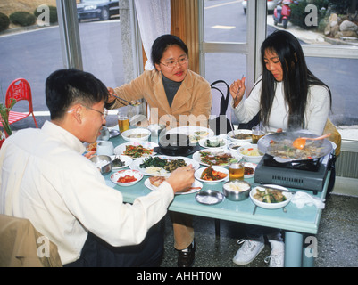 Friends eating meal in typical restaurant in South Korea - Stock Photo