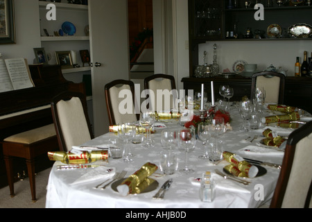 dining room table set for Christmas Dinner with Pohutukawa flower arrangement festive setting in a private home - Stock Photo