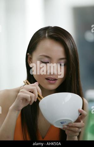 Asian woman eating using chopsticks - Stock Photo