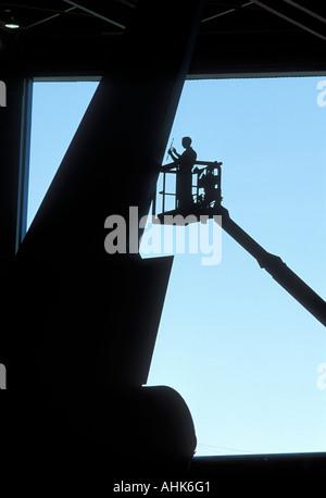 USA Washington Everett Engineer in crane works on tail section of Boeing 747 jet inside construction hangar - Stock Photo
