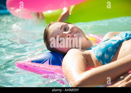 Girl on float in swimming pool - Stock Photo