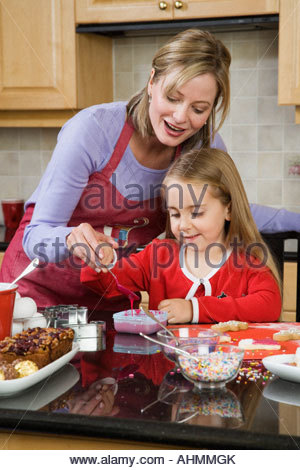 Mother helping daughter decorate a cake - Stock Photo