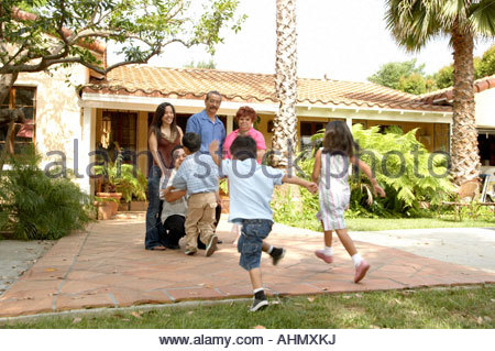 happy hispanic family in front of their new house and sold