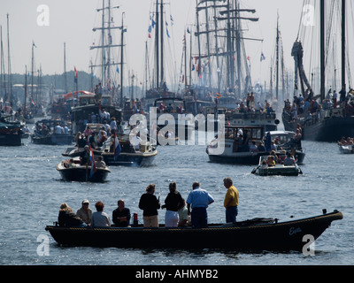 Spectators in their boat watching the Sail Amsterdam 2005 tall ship event parade the Netherlands - Stock Photo