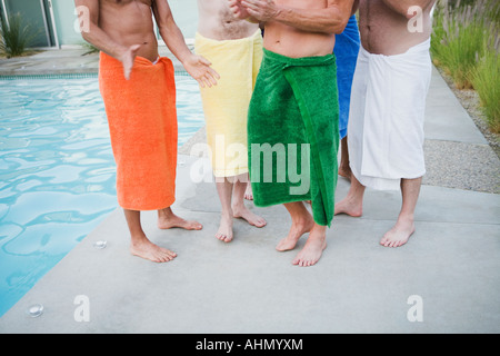 Men in towels by swimming pool - Stock Photo