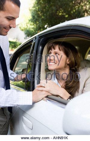 Man Talking To Woman Through Car Window Stock Photo