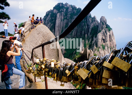 Locks on railing of Huangshan's Jade Screen Terrace with Heavenly Capital Peak in background placed by romantic - Stock Photo