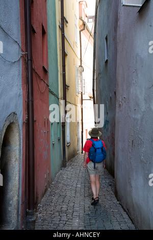 Backpacker walking through narrow alleyway between the medieval Spalicek buildings Cheb Czech Republic - Stock Photo