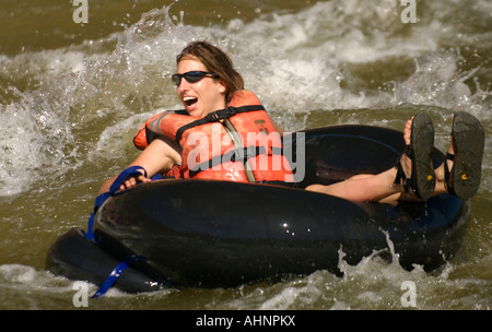 A young woman wearing sunglasses and an orange lifejacket smiles and yells as she floats on an inner tube - Stock Photo