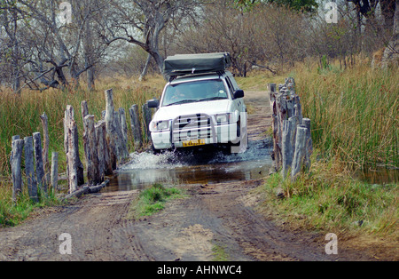 Offroad car 4x4 in botswana road over danger wooden bridge - Stock Photo