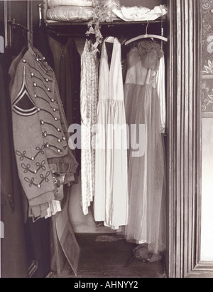 Military uniform and old ball gowns hanging in a closet. - Stock Photo