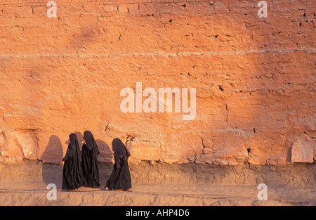 Muslim women robed in black burqas walking along the outer wall path of Karnak Temple Nr Luxor Egypt Photo by Jamie - Stock Photo