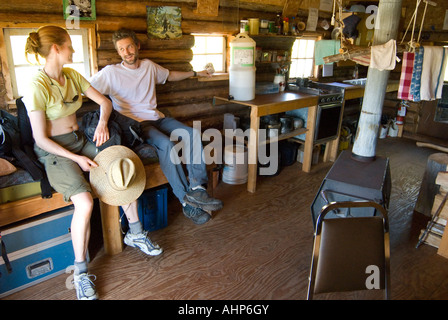 A couple takes a break from hiking in one of the cabins along the Kludahk Trail on Vancouver Island BC - Stock Photo