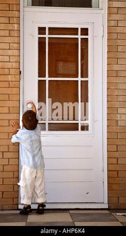 Young boy trying to open door in Moose Jaw in scenic Saskatchewan Canada - Stock Photo